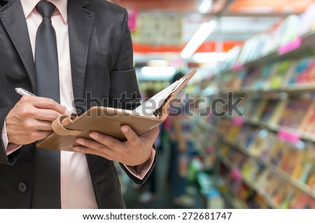 Businessman writing the note book on Abstract blurred photo of book store background - stock photo