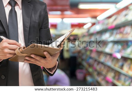 Businessman writing the note book on Abstract blurred photo of book store with people background - stock photo