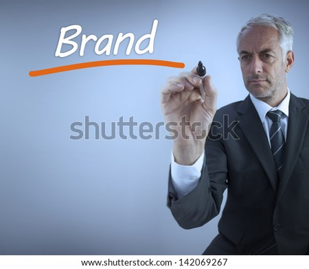 Businessman writing the word brand with a marker - stock photo