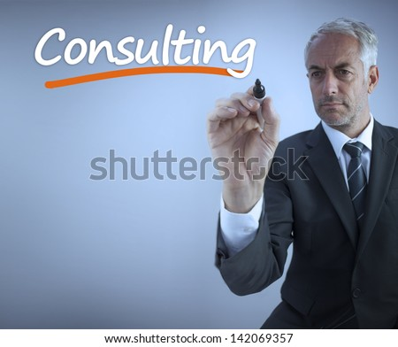 Businessman writing the word consulting with a marker - stock photo