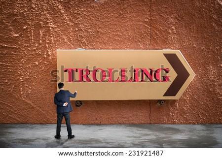 Businessman writing TROLLING  - stock photo
