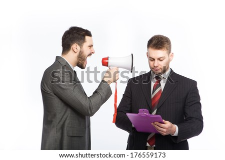 Businessman yelling through a megaphone at a colleague who has a clipboard in hand - stock photo