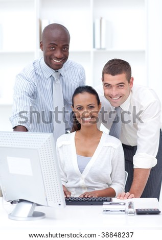 Businessmen and businesswoman using a laptop in office - stock photo