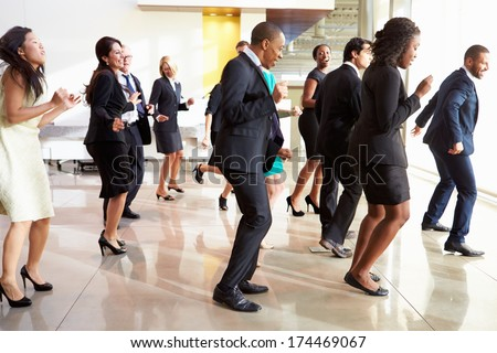 Businessmen And Businesswomen Dancing In Office Lobby - stock photo