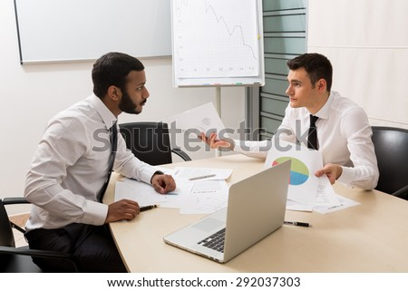 Businessmen are actively discussing the project. Successful young guys. - stock photo