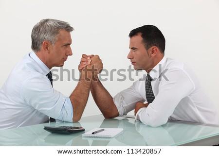 Businessmen arm wrestling - stock photo