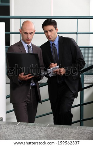 Businessmen comparing notes in stairwell - stock photo