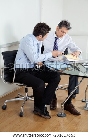 Businessmen discussing paperwork at desk in office - stock photo