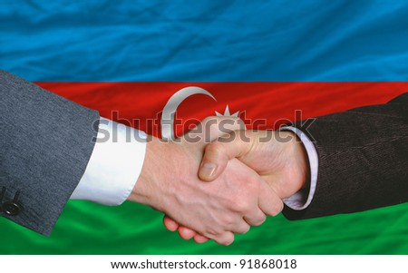 businessmen handshake after good deal in front of azerbaijan flag - stock photo
