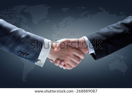 Businessmen Handshake. Hands holding on Dark Background - stock photo