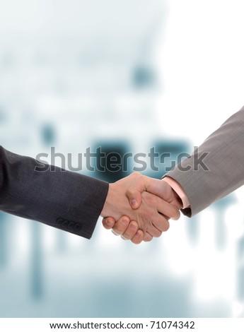 Businessmen handshake in a light business environment - stock photo