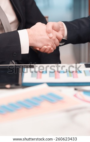 Businessmen handshaking. Cropped image of two confident business men handshaking and smiling while sitting at the table together with their colleagues - stock photo