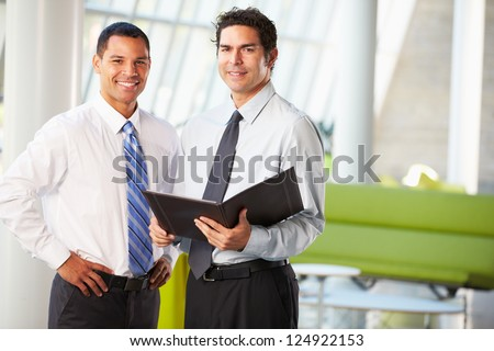Businessmen Having Informal Meeting In Modern Office - stock photo
