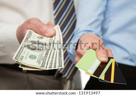 Businessmen holding credit card and money - closeup shot - stock photo