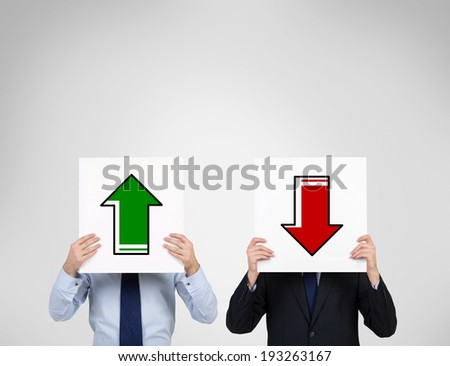Businessmen holding two arrows. - stock photo
