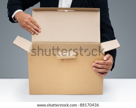 Businessmen in black suit Open blank brown paper box - stock photo