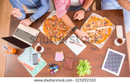 Businessmen in casual style use computers in office and eat pizza - stock photo