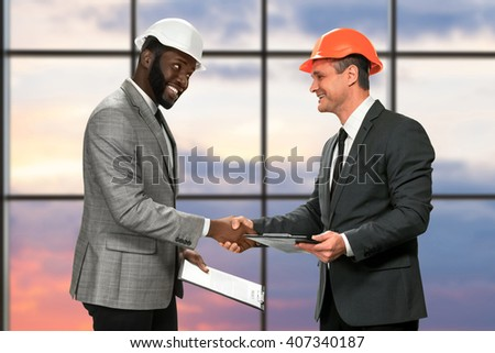 Businessmen in hardhats shaking hands. Smiling construction managers at sunrise. This project is ready. Thanks for cooperation. - stock photo