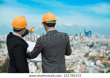 Businessmen in hardhats taking a look at the blueprint in urban environment - stock photo
