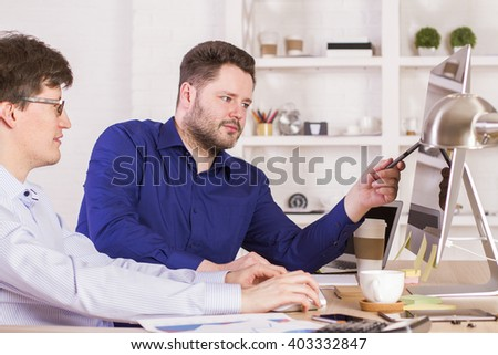 Businessmen in office looking at blank display and discussing something - stock photo