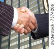Businessmen in pinstripe suits shake hands. - stock photo