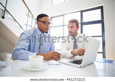 Businessmen looking at laptop and interacting at a meeting in office - stock photo