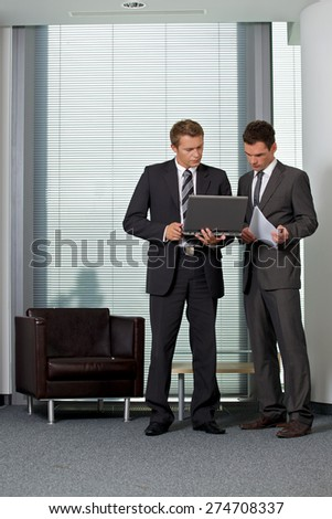 Businessmen looking at laptop in office - stock photo