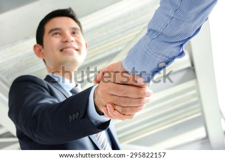 Businessmen making handshake with smiling face - greeting, dealing, merger and acquisition concepts - stock photo