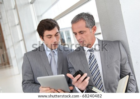 Businessmen meeting in hall with agenda - stock photo