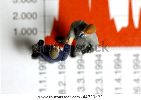 businessmen miniature figurines shaking hand on a graph - stock photo