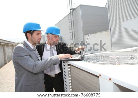 Businessmen on industrial site - stock photo