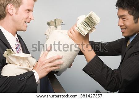 Businessmen passing money - stock photo