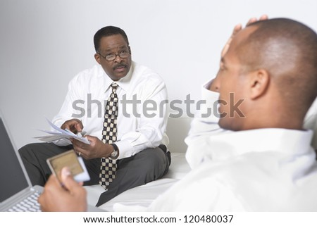 Businessmen paying heavy financial expenses - stock photo