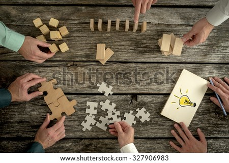 Businessmen planning business strategy while holding puzzle pieces, creating ideas with light bulb drawn on paper and rearranging wooden blocks. Conceptual of teamwork, strategy, vision or education.  - stock photo