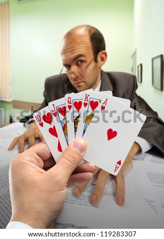 Businessmen playing poker at office - stock photo