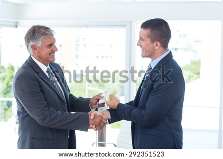 Businessmen shaking hands and exchanging money in an office - stock photo