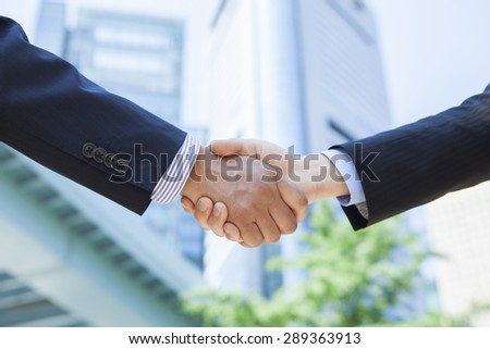 Businessmen shaking hands at office district - stock photo