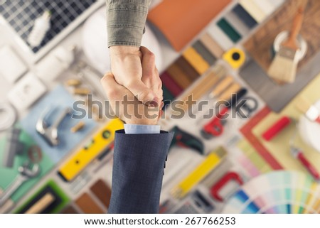 Businessmen shaking hands, construction and home renovation tools on background, top view - stock photo