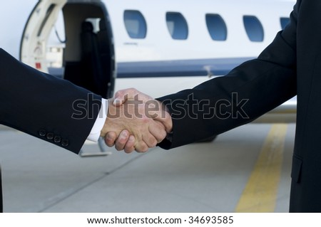 Businessmen shaking hands in front of corporate jet.  Focus on hands - stock photo