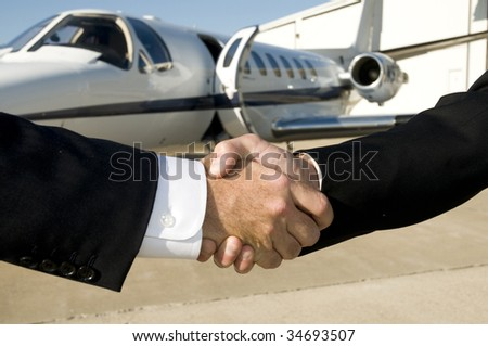 Businessmen shaking hands in front of corporate jet on ramp - stock photo