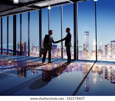 Businessmen Shaking Hands With City View - stock photo
