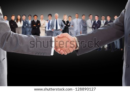 Businessmen shaking hands with large business team behind them on black background - stock photo