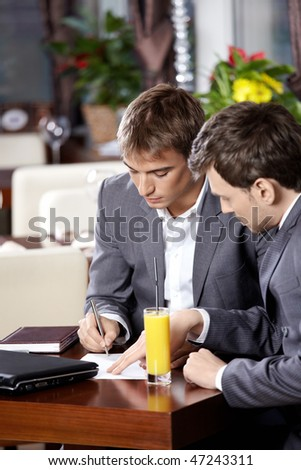 Businessmen sign the important documents at restaurant - stock photo