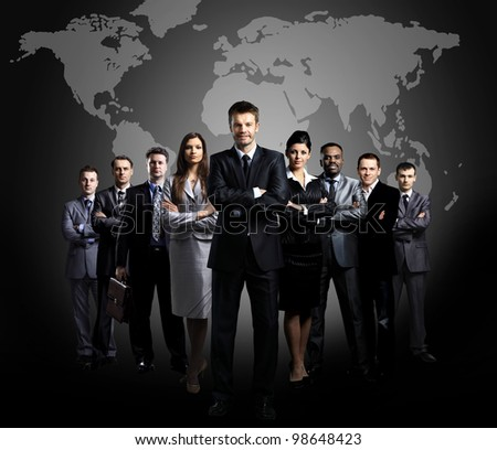 Businessmen standing in front of an earth map - stock photo