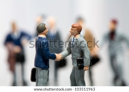 Businessmen standing on a statistical document shaking hands cheered on by the team - stock photo