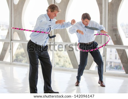 Businessmen taking a play Break hula hooping in a modern office to get ideas flowing - stock photo