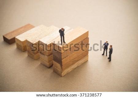 Businessmen talking about wood block step, Successive business concept. - stock photo