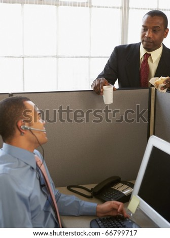 Businessmen talking over cubicle wall - stock photo