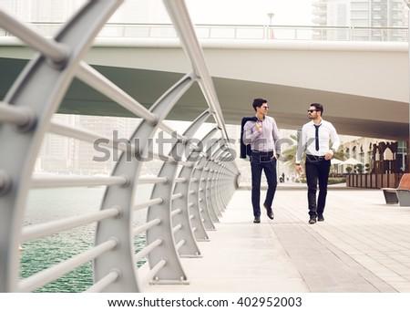 Businessmen walking at Dubai Marina. - stock photo