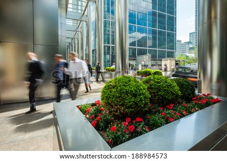 Businessmen walking outside of modern office buildings - stock photo
